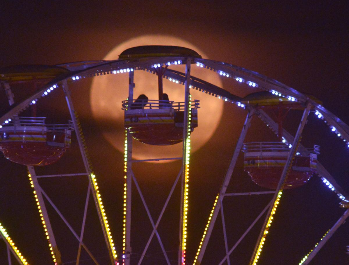 A full moon silhouettes riders at the 61st Annual Alabama National Fair in Montgomery on, Oct. 8. (Lloyd Gallman/Montgomery Advertiser via Associated Press)