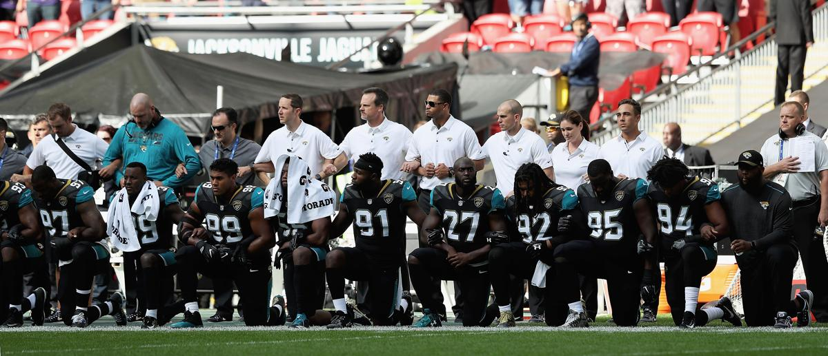 Jaguars players take a knee before facing the Ravens in London.
