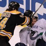 Boston Bruins defenseman Adam McQuaid lays a heavy hit on Canucks right wing Maxim Lapierre.