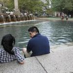 Johanna Escobar, left, of Boston, talks to Andrews Arenes, of Somerville, during a break from work to relax at the fountain Thursday at Copley Square in Boston.