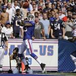 Buffalo Bills' Stevie Johnson (13) makes a touchdown catch under pressure from New England Patriots' Devin McCourty (32) during the first half of an NFL football game in Orchard Park, N.Y., Sunday, Sept. 25, 2011. (AP Photo/Gary Wiepert)
