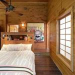 The cabin sits on 69 acres, most of it conservation land; an attached garage was converted into a high-ceilinged master bedroom, which a ceiling fan cools in summer.