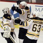 Bruins goaltender Tim Thomas, Johnny Boychuk, and Brad Marchand are uplifted after a shootout victory in Chicago.