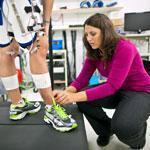 Cara L. Lewis, an assistant professor of physical therapy, fits Kaitlyn Chin with a robotic hip device.