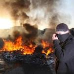 An activist covered his face while walking past a burnt caravan yesterday as police moved to begin evicting Irish Travelers from a camp in Basildon, England, where they'd lived for more than a decade. Police said officers were attacked with rocks and other missiles. Residents and supporters, however, said police used excessive force.