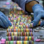 A worker sorted Necco Wafers for packaging. Each roll contains a mix of the candy's eight flavors.