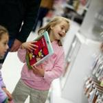 (Dedham, MA- Saturday, November 12, 2011)-- Erin Flack, 7, of Needham is excited about an Angry Birds iPad cover in Toys R Us's newly expanded electronics section. She was shopping with sister, Maeve, on left, age 5 and dad, Paul. Earlier she had been texting her mother with her father's Blackberry. for Michael Farrell story/Business Section Photo by Rose Lincoln for the Boston Globe