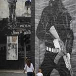 A mural of a paramilitary gunman reminds mostly Protestant East Belfast of the city's violent history.