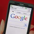 A posed picture shows a Motorola Droid phone displaying the Google search page in New York August 15, 2011. Google Inc. will buy phone hardware maker Motorola Mobility Holdings Inc. for $12.5 billion to bolster adoption of its Android mobile software and compete with smartphone rival Apple Inc. In its biggest deal to date, Google said it would pay $40 per share in cash, a 63 percent premium to Motorola Mobility's Friday closing price on the New York Stock Exchange. REUTERS/Brendan McDermid (UNITED STATESSCI BUSINESS - Tags: BUSINESS SCI TECH IMAGES OF THE DAY)