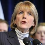 Martha Coakley's action escalates a dispute with Ally Financial, which said it would no longer buy new home loans here.