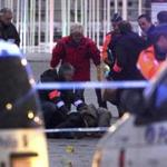 Police officers and experts surround a dead body at the Place Saint Lambert square where a man threw explosives in the city center of the Belgian city of Liege December 13, 2011. A gunman killed four people, including himself, in an attack in Liege on Tuesday, Belgian media reported. REUTERS/Thierry Roge (BELGIUM - Tags: CONFLICT SOCIETY DISASTER)