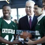Members from the Cathedral High School football team posed with Mayor Menino and presented him with a footbal at Legal Harborside in Boston today.