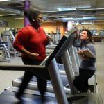 Tania Cooper, exercising at Healthworks Community Fitness, is monitored by wellness coach Ashley Norwood.