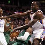 Former Celtic Kendrick Perkins got tangled up under the basket with Rajon Rondo.