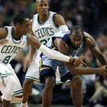 Memphis Grizzlies' Sam Young, right, keeps the ball away from Boston Celtics' Rajon Rondo (9) as Celtics Ray Allen, center, looks on in the second quarter of an NBA basketball game in Boston, Sunday, Feb. 5, 2012. (AP Photo/Michael Dwyer)