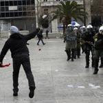 A protester hurled rocks at riot police today in Athens, Greece.