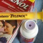 A container of grape-flavored Infants' Tylenol liquid medicine with the enclosed syringe and flow restrictor.