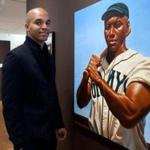 Artist and author Kadir Nelson with one of his picture-book paintings, of Josh Gibson, on display at the Eric Carle Museum of Picture Book Art in Amherst