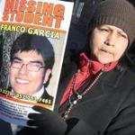 Luzmila Garcia, mother of missing Boston College evening student Franco Garcia, held a poster in front Mary Ann's Bar on Beacon Street yesterday.