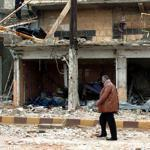 A man walked near a blast site in the southern Syrian town of Deraa today.