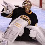 A grimacing Tuukka Rask tumbles backward after injuring his left leg while making an awkward save.