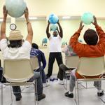 Instructor Garry Sanon leads a chair exercise class at Kit Clark Senior Services in Dorchester.