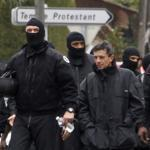 Masked French special unit policemen (RAID) left the scene after the assault to capture gunman Mohamed Merah.