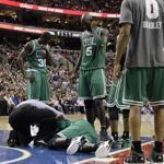 The Celtics players gathered around an injured Mickael Pietrus in the first half of their game against the 76ers.