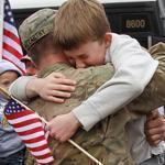Robert McCarthy of Braintree greeted his 10-year-old son Liam at the Braintree Armory.