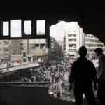 Syrian youth stood in a building that was hit by tank shells in a neighborhood of Damascus after a raid by troops Thursday.