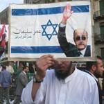 A man held a sign with an image of the Israeli flag and a photo of presidential candidate and former intelligence chief Omar Suleiman in Tahrir square in Cairo on Friday.