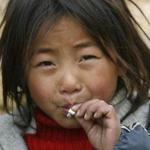 A child from the Yi ethnic minority smokes a cigarette in Sichuan, China.