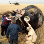 Russia's space agency ground personnel checked the Soyuz capsule shortly after landing on the sweeping steppes of central Kazakhstan, ending the men's 163-day stay on the International Space Station.