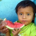 A boy feasts on a hunk of watermelon in a small town beside Lake Atitlan in Guatemala. PHOTO CREDIT DAVID ABEL