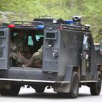 Officers in an armored vehicle headed toward the scene of a standoff at an underground bunker in the woods in North Bend, Wash., on Friday.
