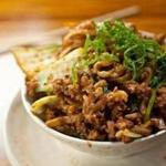 Top: Dan dan mein, noodles topped with a spicy pork and mushroom ragu.