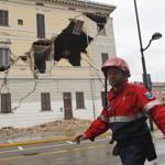 A civil protection volunteer walked past the damaged town hall building in St. Agostino, Italy, Sunday.