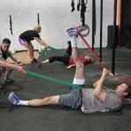 In Boston, CrossFit trainer Christina Morris (second from left), helps Brian Bostwick (left) hold a cord for workout partner Kevin Cummings.