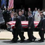 Pallbearers loaded the casket of slain Springfield police officer Kevin Ambrose into the hearse following his funeral at St. Catherine of Sienna Church Friday.