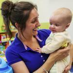 Danielle DeCarlo worked with 7-month-old Alex Filandrianos and 4-month-old Davis Wiser at a Little Sprouts day-care center in Brighton. An influx of new students has put teachers back in demand at the company, which has 16 Boston locations.