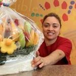 Iris Matos carves fruit into bouquets and other creations as the production manager at at Edible Arrangements.