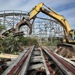 Earl Thibeault powers a machine as he demolishes the Comet roller coaster at the defunct Lincoln Park amusement park in Dartmouth, Mass., Wednesday July 11, 2012. The crumbling roller coaster is being cleared for a development that will include single-family homes, apartments and commercial space. (AP Photo/The Standard-Times, Peter Pereira)