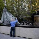 Workers raised the corporate flag of JPMorgan Chase at the bank's headquarters in New York on Friday.