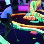 Alexis Medeiros (left) and Nathan Vieira played a round of miniature golf at Oceans 18, which has a glow-in-the-dark course.