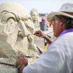 Justin Gordon of Groveland carved out one of the faces on his sand sculpture at the competition on Revere Beach Friday.