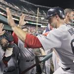 Daniel Nava (center) is congratulated in the dugout after he scored the go-ahead run on a single by Mike Aviles in the ninth inning against the Rangers.