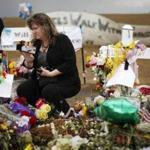 Sheri Jaramillo, cousin of Jonathan Blunk, who was killed in the attack, looked at his cross at a memorial in Aurora, Colo.