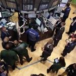 Traders and floor officials gathered at a post on the floor of the New York Stock Exchange shortly after the beginning of trading on Wednesday.