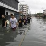 Residents waded across a flooded area north of Manila. Seasonal rains followed last week's drenching by Typhoon Saola.