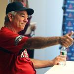 Backed by his owner and GM, Red Sox manager Bobby Valentine responds to a pregame media question about his job safety by giving a thumbs up.